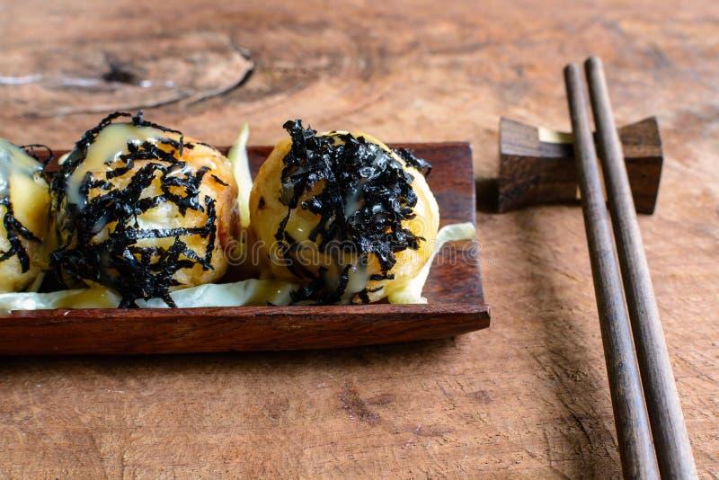 Takoyaki op houten lijst met eetstokjes stock foto