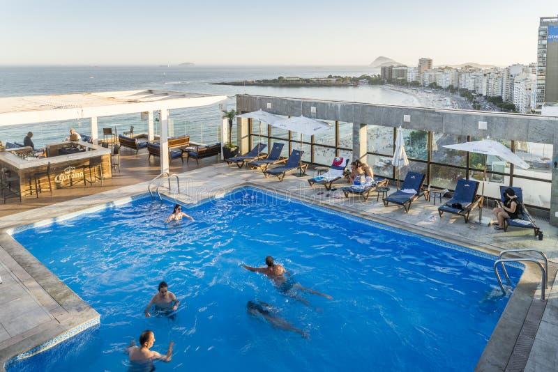 Taksikten av simmare på en lyxig hotelltakvåningpöl och stången som förbiser Copacabana, sätter på land i Rio de Janeiro, Brasili royaltyfria foton