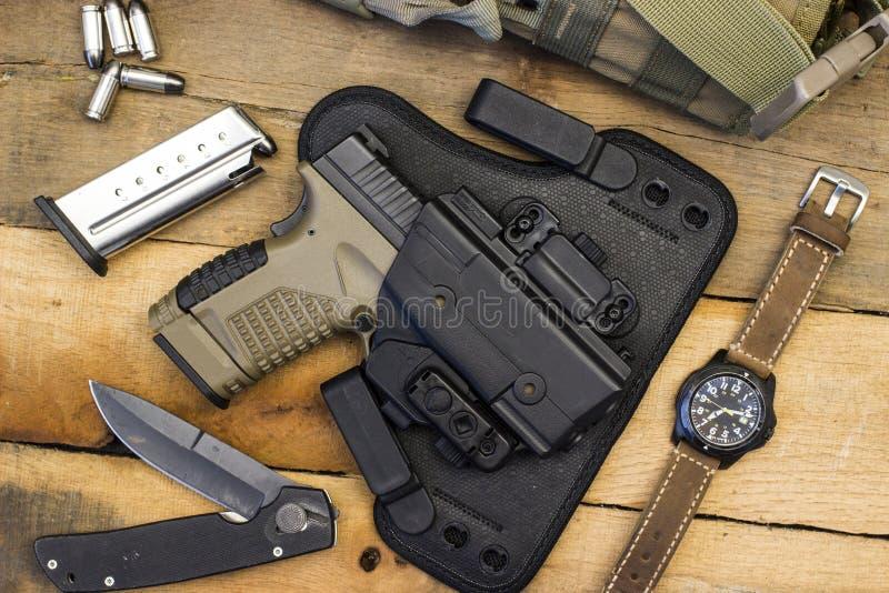 Taktisk handeldvapen och kugghjul inklusive klockan, kulor, kniv, pistolhölster, påse arkivfoton