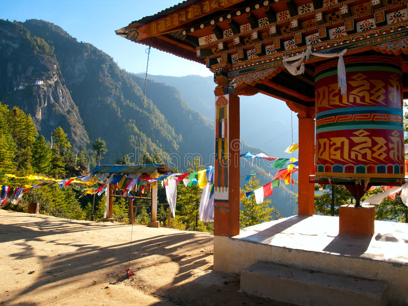 Taktshang monastery in Paro (Bhutan). View of the Taktshang monastery in Paro (Bhutan) with prayer flags and a prayer wheel in the front stock image