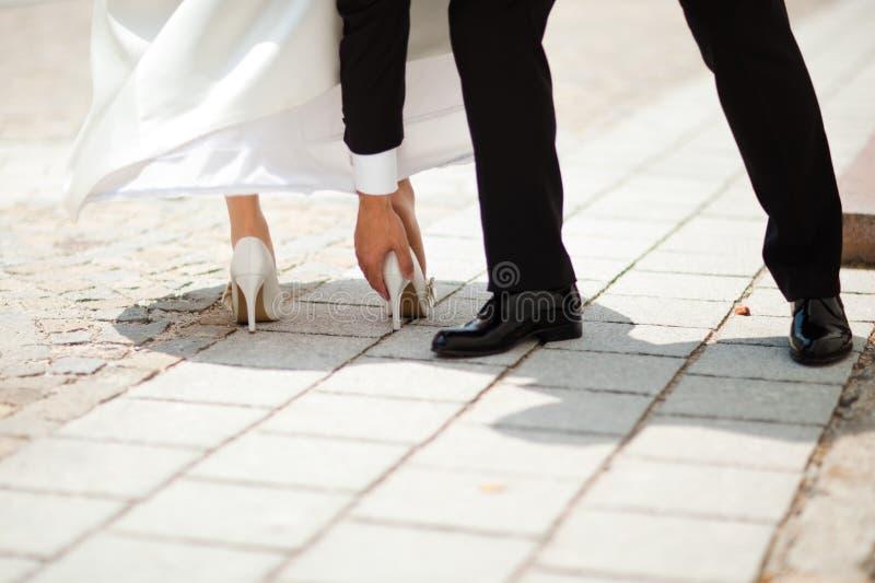 Talón de la boda pegado en pequeño hueco en la pavimentación - el novio está ayudando - del momento torpe antes de ceremon fotografía de archivo