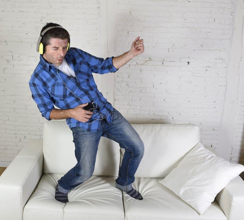 20-tal eller 30-talmannen hoppade på soffan som lyssnar till musik på mobiltelefonen med hörlurar som spelar Air Guitar royaltyfria bilder