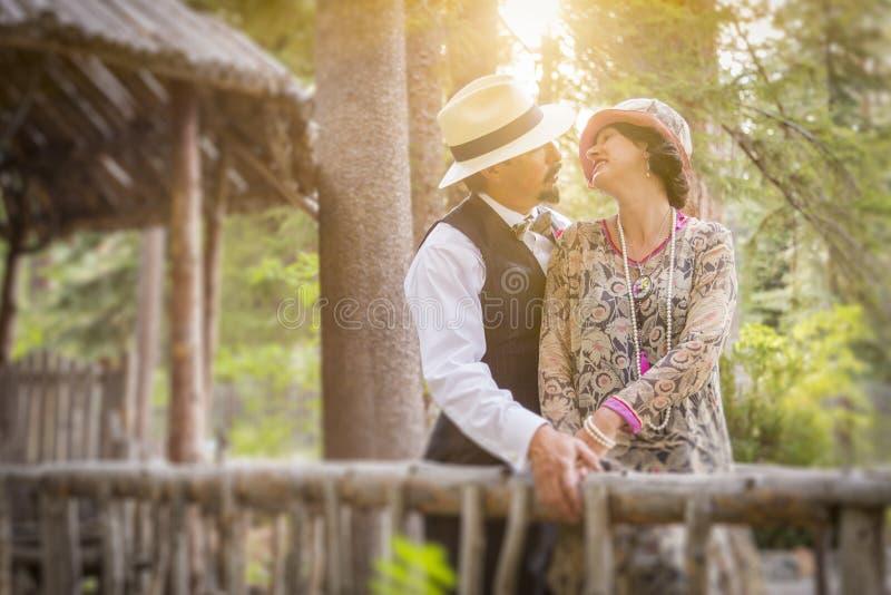 20-tal klädde romantiska par på träbron arkivbilder