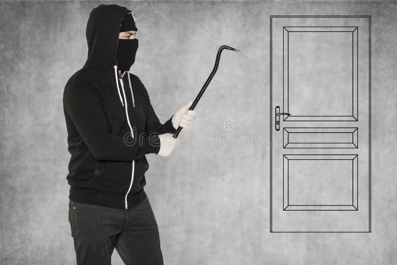 Tal puerta es fácil para un ladrón, palanca en manos fotografía de archivo libre de regalías