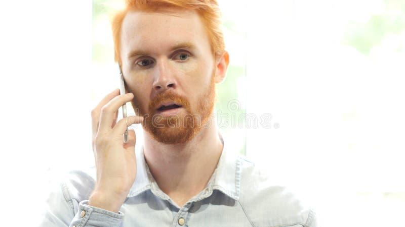 Tala på telefonen, ung röd hårskäggman som diskuterar nytt projekt arkivfoton