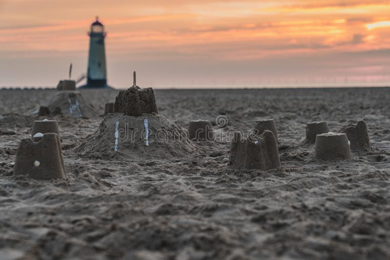 Talacre Lighthouse, Clwyd, Wales, UK. Sandcastles on the beach, with evening clouds and the Point of Ayr Lighthouse in the background, near Talacre, Flintshire stock images