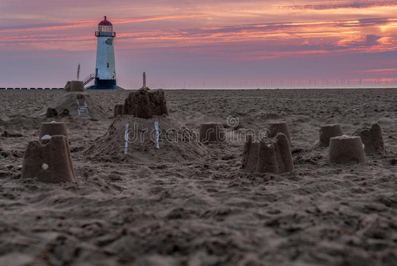Talacre Lighthouse, Clwyd, Wales, UK. Sandcastles on the beach, with evening clouds and the Point of Ayr Lighthouse in the background, near Talacre, Flintshire stock image