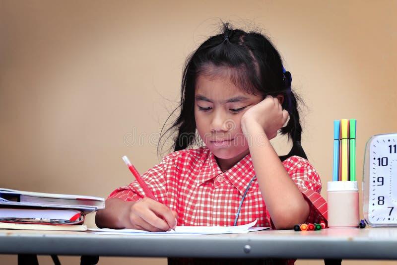 Taladro asiático del niño al hacer la preparación en casa foto de archivo