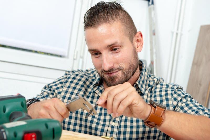 Taladro de medición del hombre joven usando el calibrador fotografía de archivo