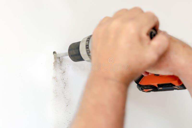 Taladro de poder de tenencia del hombre del primer a disposición y haciendo el agujero en la pared blanca DIY Reparación y renova fotos de archivo