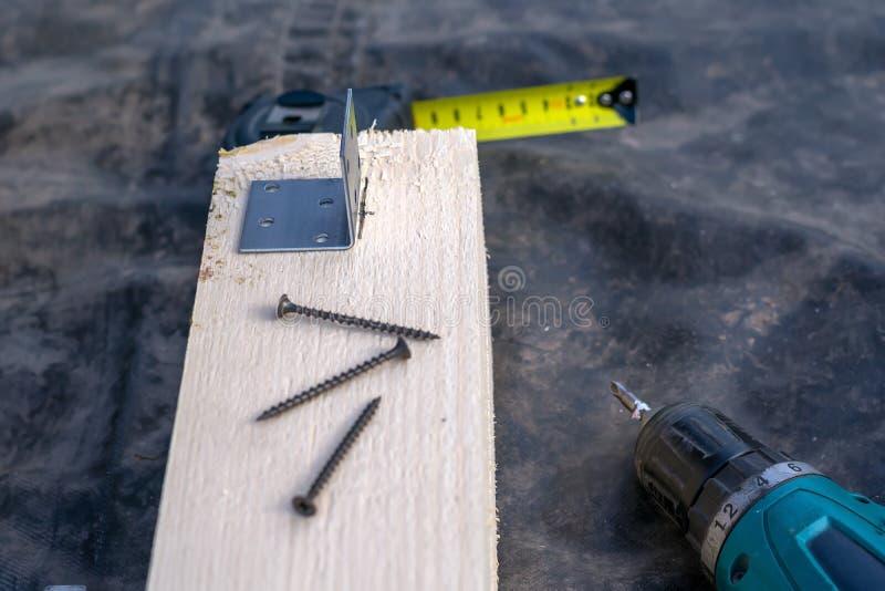 Taladro, destornillador, tornillos y regla en el tablero de madera fotografía de archivo libre de regalías