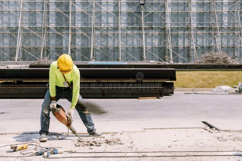 Taladro eléctrico del trabajador de construcción que perfora la tierra concreta adentro imagen de archivo libre de regalías
