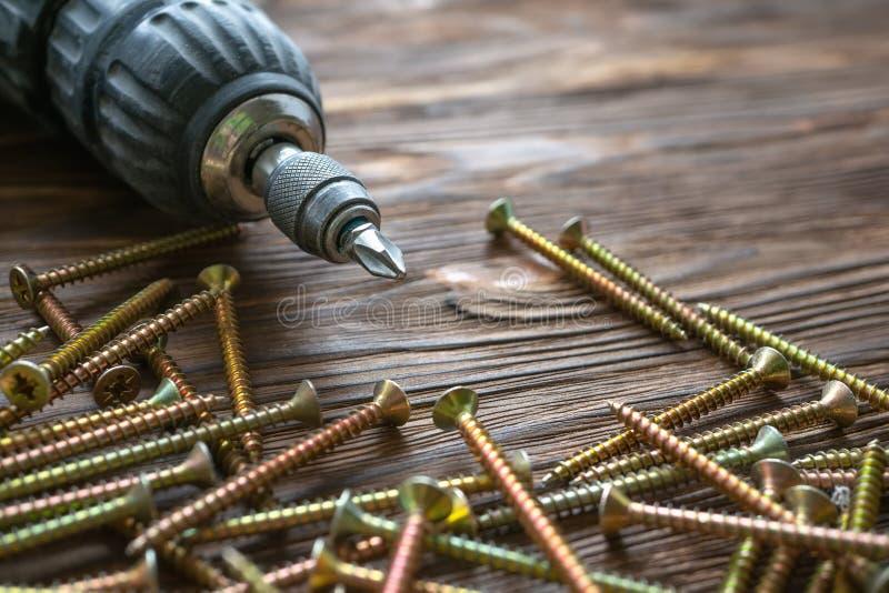 Taladro, tornillos y pasadores en el fondo de madera imagenes de archivo