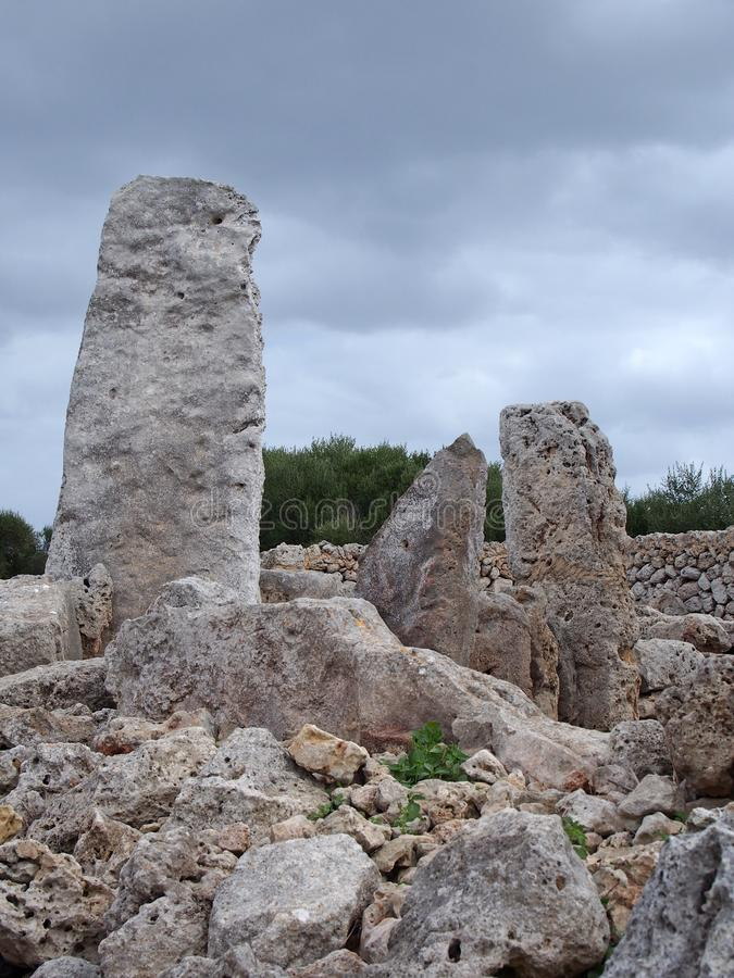 Talaiotic village of Trepuco Minorca Balearic Islands showing a large megalith and taula in the background. The Talaiotic village of Trepuco Minorca Balearic royalty free stock photos