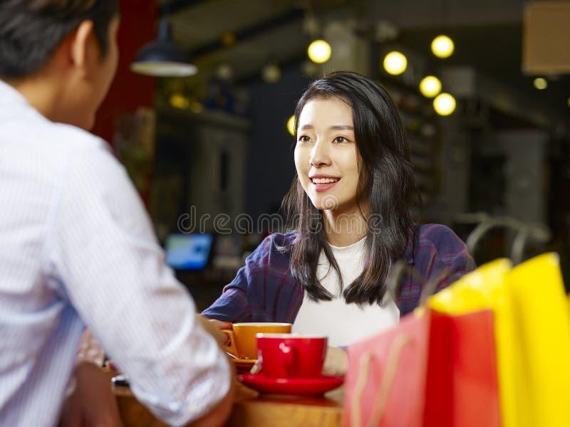 Talande framsida för unga asiatiska par - till - framsida i coffee shop royaltyfria bilder
