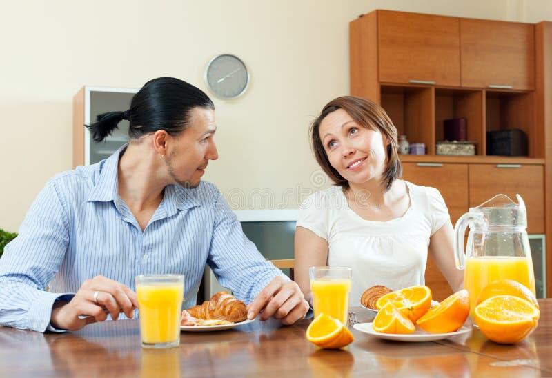 Talande frukosttid för lyckliga par royaltyfria foton