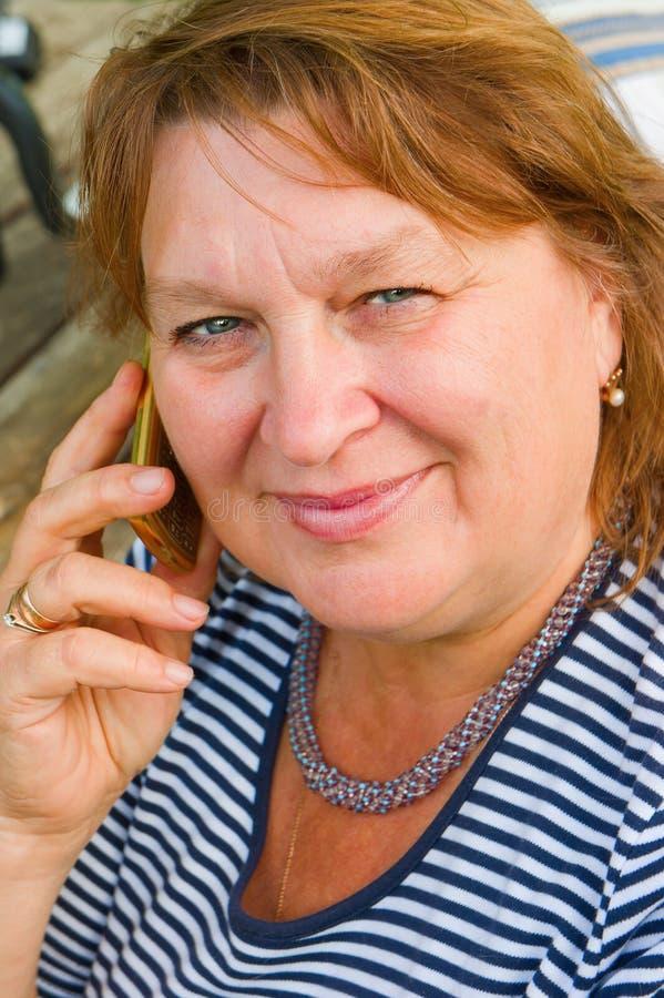 talande kvinna för åldrig medeltelefon royaltyfri foto