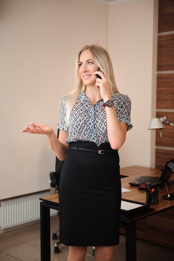 talande kvinna för härlig telefon för affär mobil Ungt kvinnligt modellarbete med försäljningar i regeringsställning fotografering för bildbyråer
