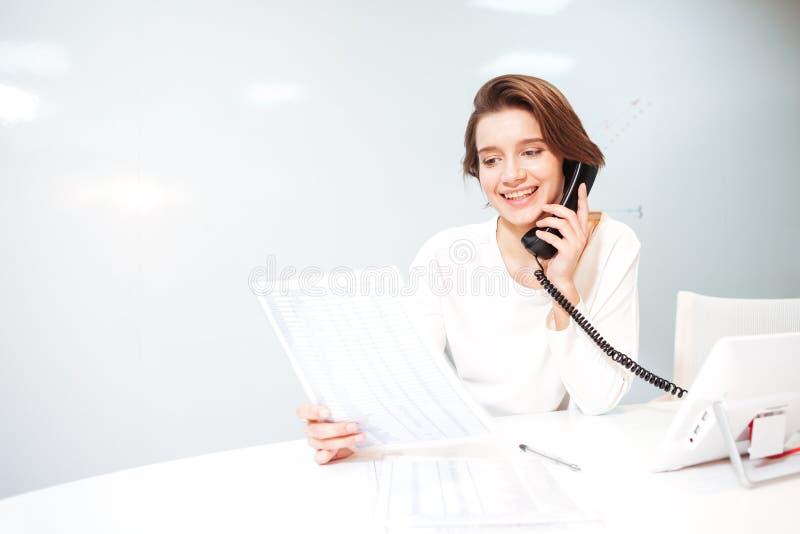 talande kvinna för kontorstelefon arkivbild