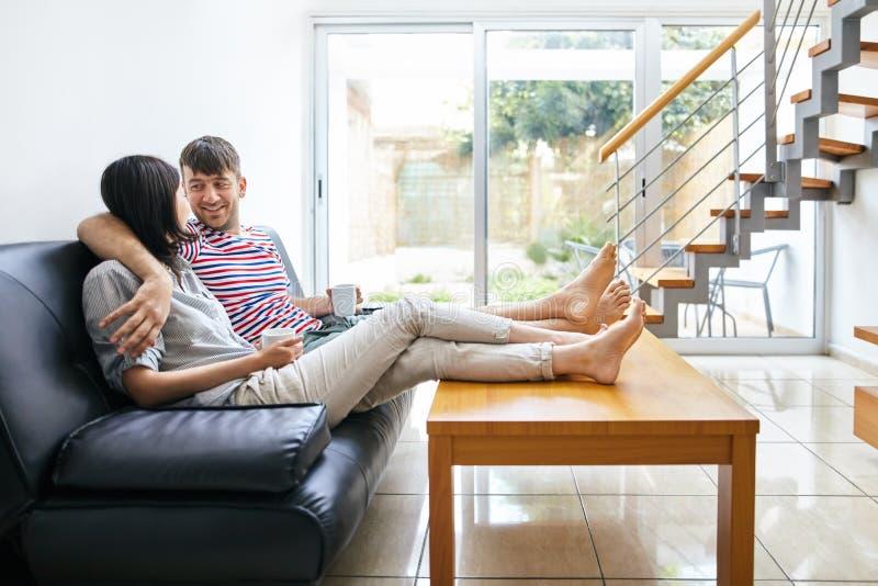 Talande sammanträde för lyckliga attraktiva par på soffan i modernt H arkivbild