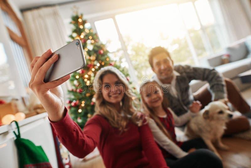 Talande selfie för ung familj under jul hemma royaltyfri fotografi