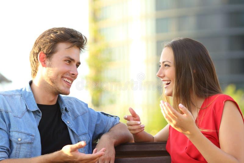 Talande sitta för lyckliga par på en bänk i gatan arkivbild