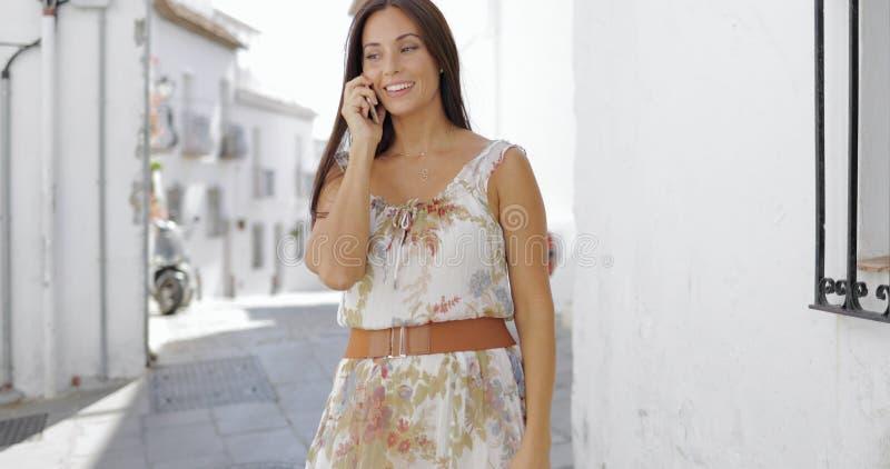 Talande telefon för charmig flicka på gatan royaltyfria bilder