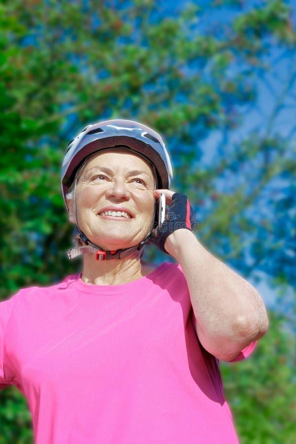 Talande telefon för hög cyklist utomhus royaltyfria foton