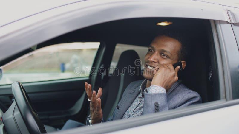 Talande telefon för lycklig affärsman för blandat lopp, medan sitta inom hans bil utomhus arkivbilder
