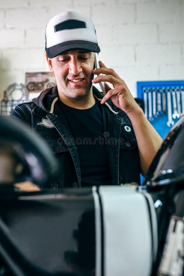 Talande telefon för mekaniker, medan fixa mopeden arkivfoton