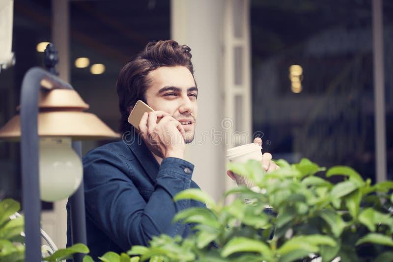 Talande telefon för ung man i kafé royaltyfri foto
