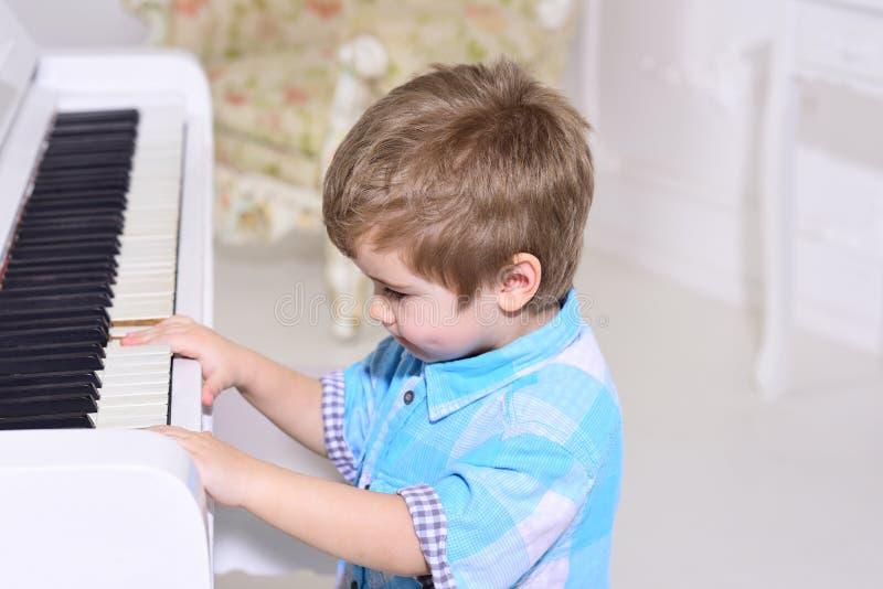 Talanted孩子 音乐 儿童游戏钢琴 愉快的童年 关心发展 音乐和艺术教育 男孩一点 免版税图库摄影