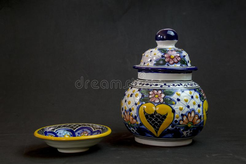 Talavera vase with a playful plate. A beautiful vase of talavera on a black background with his plate partner coming to the party stock image