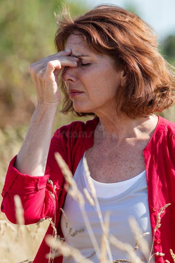 50-talbrunettkvinnan som har bihåla, och huvudvärken smärtar utomhus royaltyfria bilder