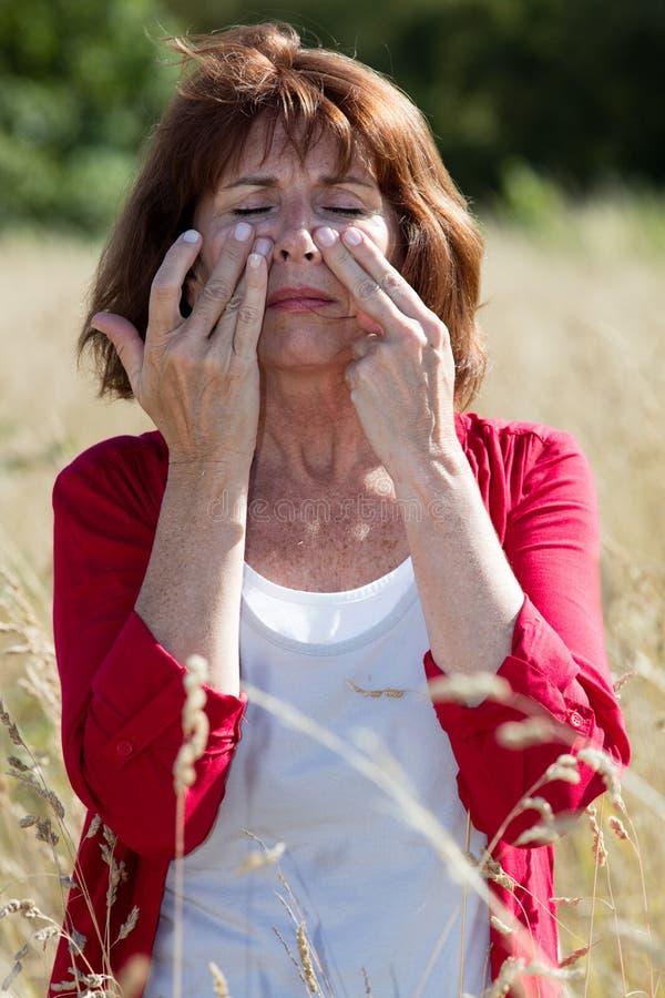 50-talbrunettkvinnan som masserar framsidan för att lugna bihåla, smärtar utomhus arkivbilder