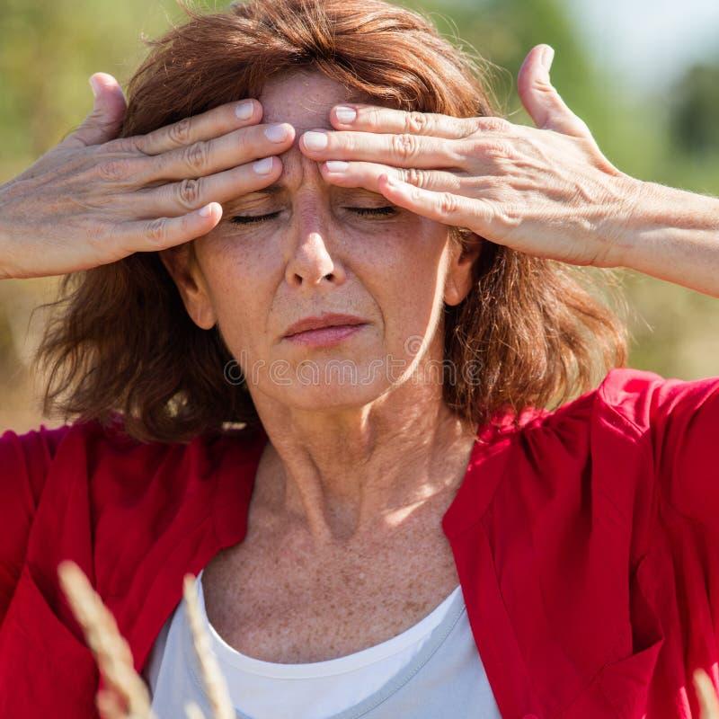 50-talbrunettkvinnan som masserar pannan för att lugna bihåla, smärtar utomhus royaltyfri fotografi