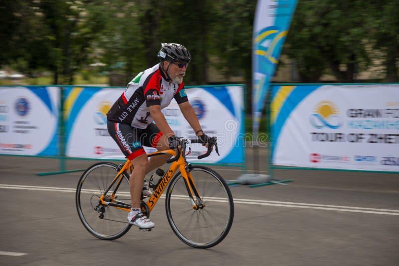 TALDYKORGAN, KAZACHSTAN - MEI 21, 2017: Een bejaarde mannelijke atleet berijdt een wegfiets stock afbeeldingen