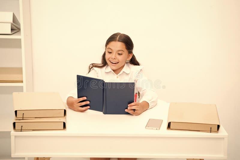 Tale argomento interessante Il bambino della ragazza ha letto il libro mentre sieda l'interno bianco della tavola Manuale della l fotografia stock