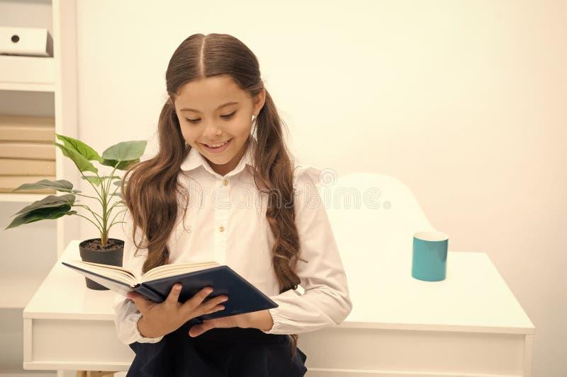 Tale argomento interessante Manuale della lettura Il bambino della ragazza ha letto il libro mentre interno bianco della tavola d fotografie stock
