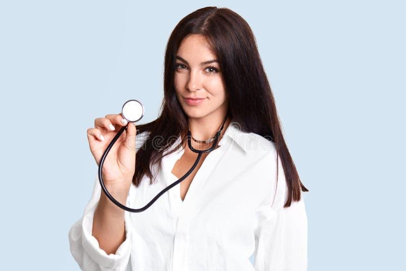 Taleneted de donkerbruine jonge vrouwelijke arts of de pediater in witte laag, phonendoscope houden, geneest kleine die kinderen, stock fotografie