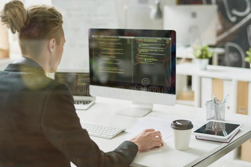 Talented coder working with computer language. Rear view of hipster coder with hair bun wearing jacket using computer while programming app and sitting at desk stock photos