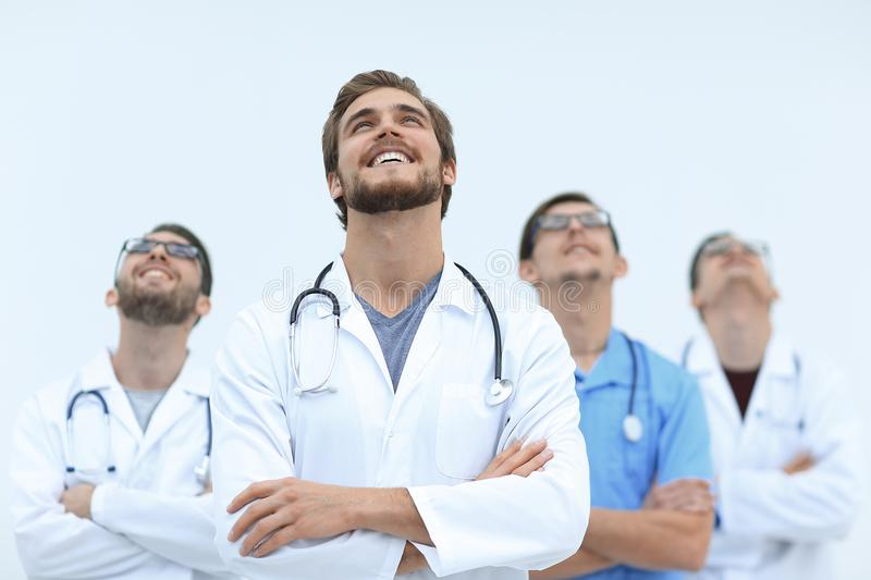 Talented doctor looking at the top, on the copy space. Isolated on white stock photography