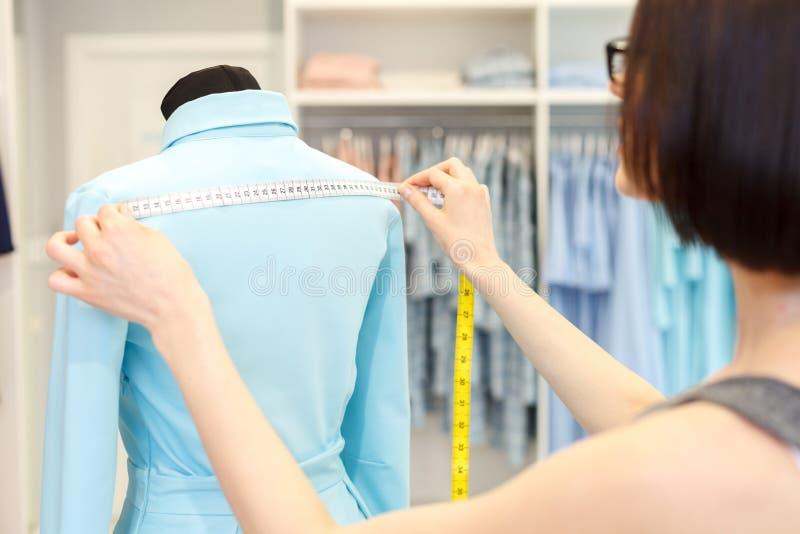 Talented fashion designer taking measurements of cloth stock photo