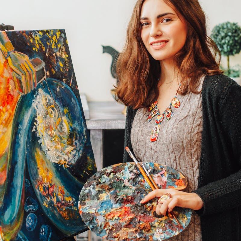 Talented female painter performing artwork studio stock images