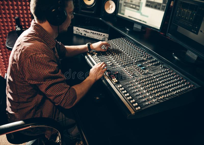 Talented guy working in the music studio. man is creating a hit stock photos