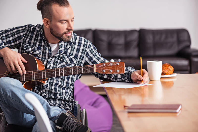 Talented handicapped guy writing song lyrics royalty free stock photography