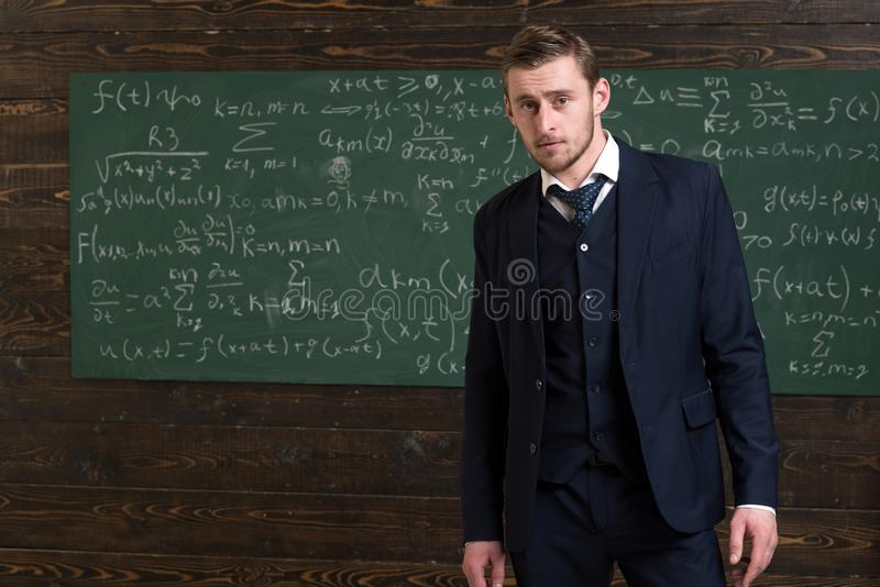Talented mathematician. Man formal wear classic suit looks smart, chalkboard with equations background. Genius solved stock photo