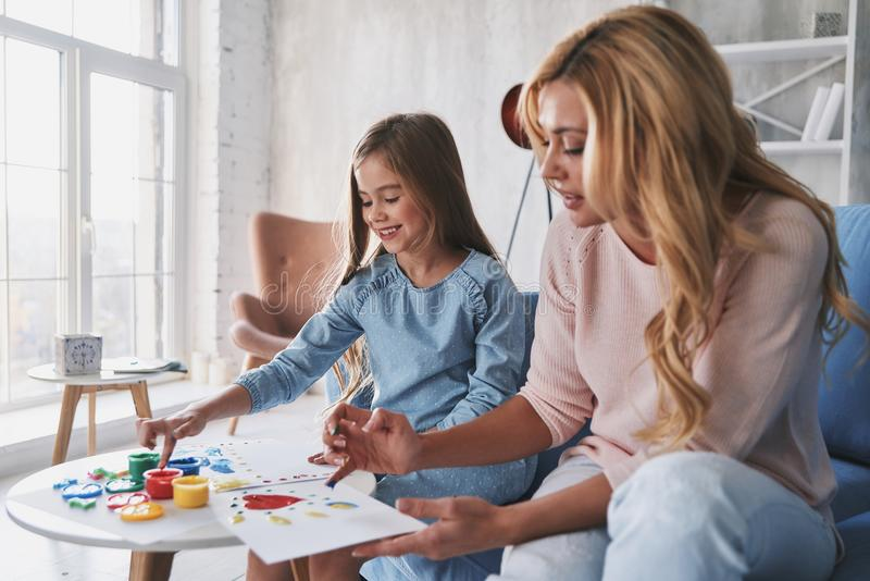 So talented! Mother and daughter painting with fingers and smiling while spending time at home royalty free stock photos