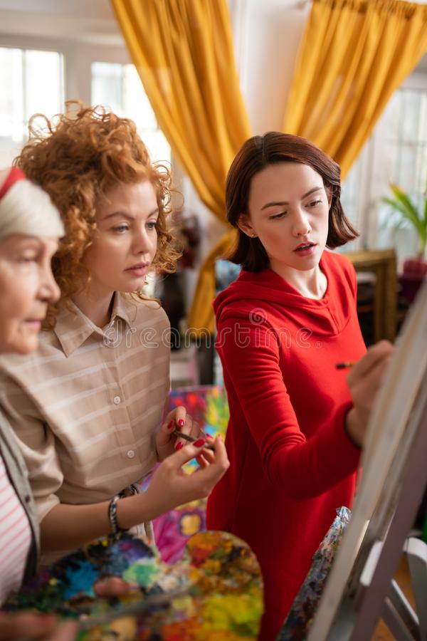 Talented women feeling inspired while painting together. Painting together. Talented and creative women feeling inspired painting together royalty free stock photos