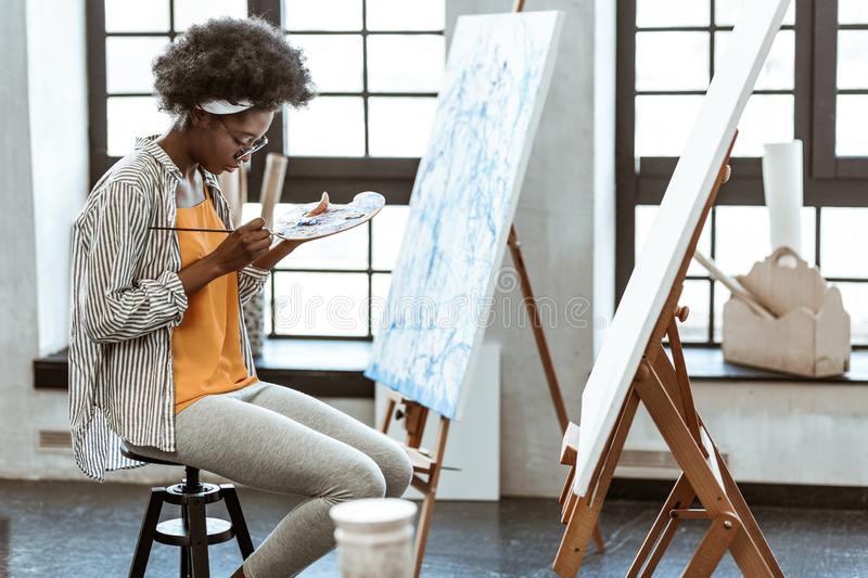 Talented young artist mixing gouache on little color palette. Mixing gouache. Talented young artist sitting on the chair while mixing gouache on little color royalty free stock image